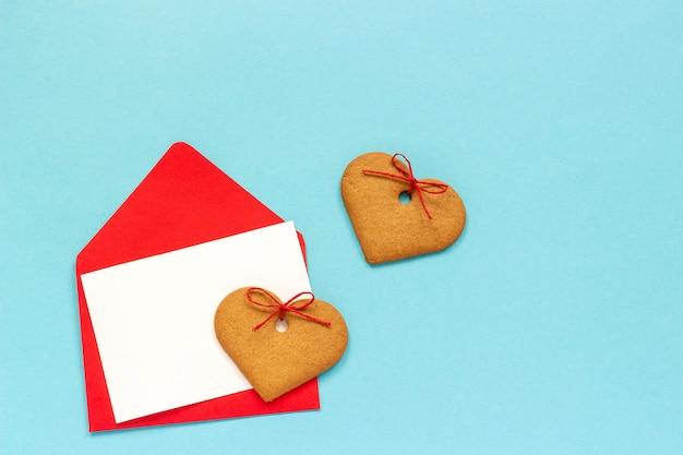 Enveloppe rouge avec une carte blanche vierge pour le texte et des biscuits au gingembre en forme de coeur