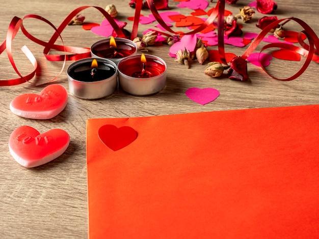 Enveloppe rouge à côté de bougies avec des pétales de rose rouges et des coeurs sur la table