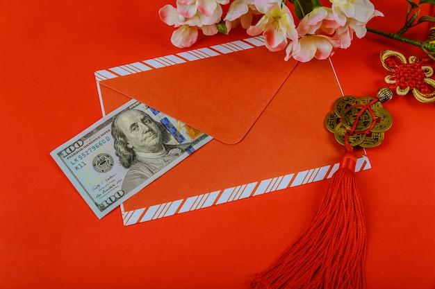 Enveloppe rouge avec un dollar pour le bonus du nouvel an chinois sur fond rouge