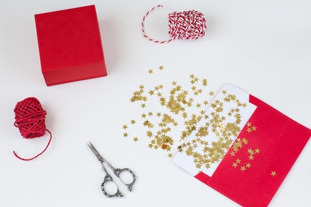 Une enveloppe rouge, des étoiles dorées, des rubans, une boîte cadeau, des ciseaux