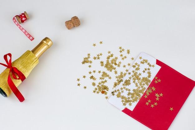 Une enveloppe rouge, des étoiles d'or, un ruban rouge et une bouteille de champagne