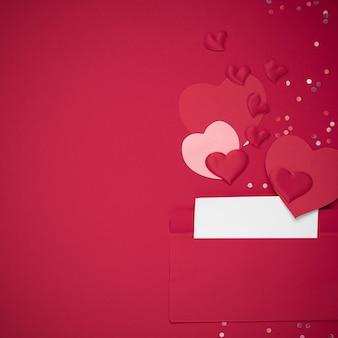Enveloppe rouge avec lettre d'amour sur fond rouge avec de nombreux coeurs autour
