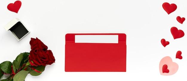 Enveloppe rouge avec lettre, bouquet de roses, nombreux coeurs et boîte pour bague sur fond blanc. vue de dessus, pose à plat
