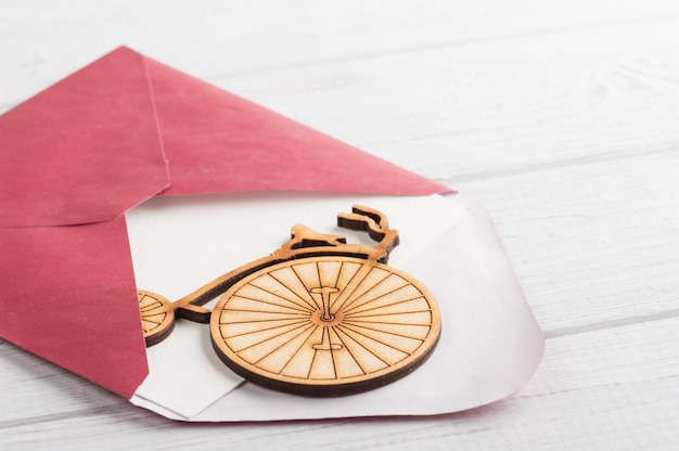 Enveloppe rouge avec papier vide et vélo en bois