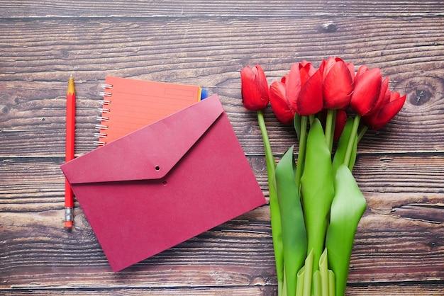 Enveloppe et tulipe rouge sur table
