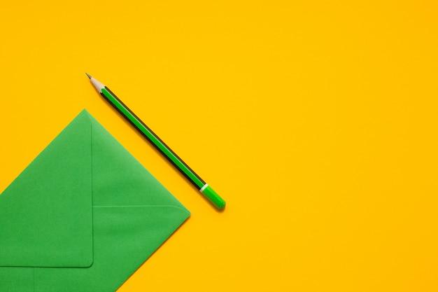 Enveloppe verte et crayon vert simple sur fond jaune, vue de dessus, avec fond.
