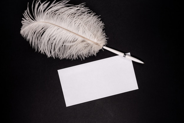 Enveloppe vide blanche avec stylo plume rétro sur fond noir