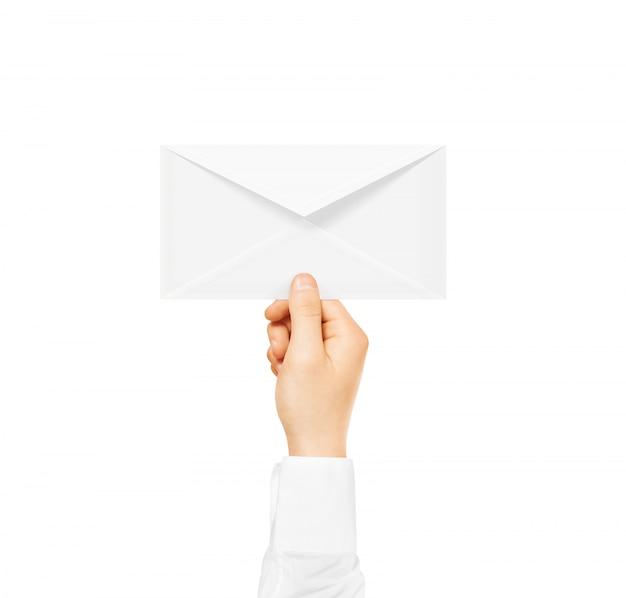 Enveloppe vierge blanche maquette tenant dans la main. document de poste vide.