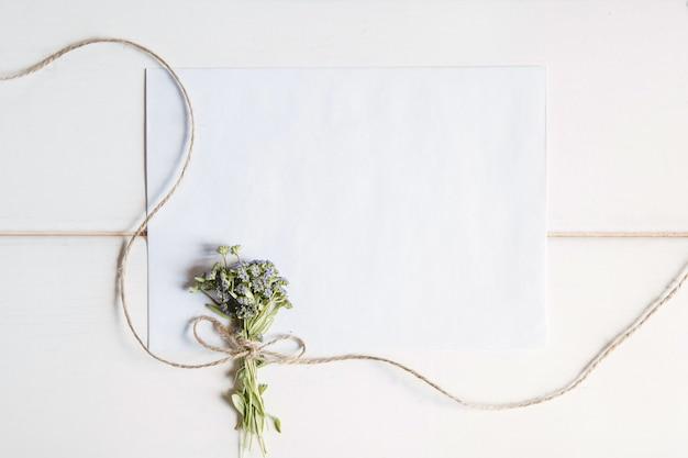 Une enveloppe vierge blanche avec un petit bouquet de fleurs sauvages attachées avec de la ficelle sur une surface en bois blanche