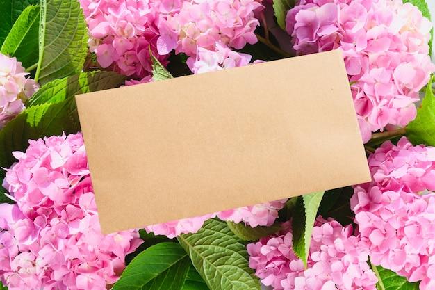 Enveloppe vierge et fleurs d'hortensia rose. copiez l'espace. carte de voeux