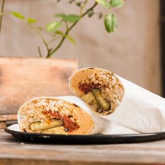 Enveloppement de burrito végétarien sur une assiette au-dessus de la table
