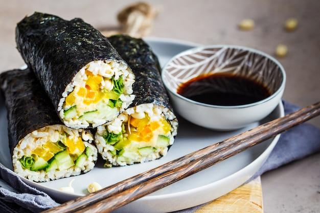 Enveloppement nori végétalien avec du riz, du houmous, des légumes et des semis.