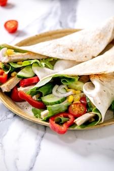 Enveloppement de tortila mexicain traditionnel avec de la viande de porc et des légumes dans une assiette en céramique sur une surface en marbre blanc. fermer. restauration rapide maison