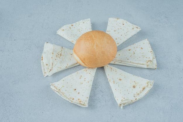 Enveloppements lavash traditionnels et pain hamburger sur une surface en marbre