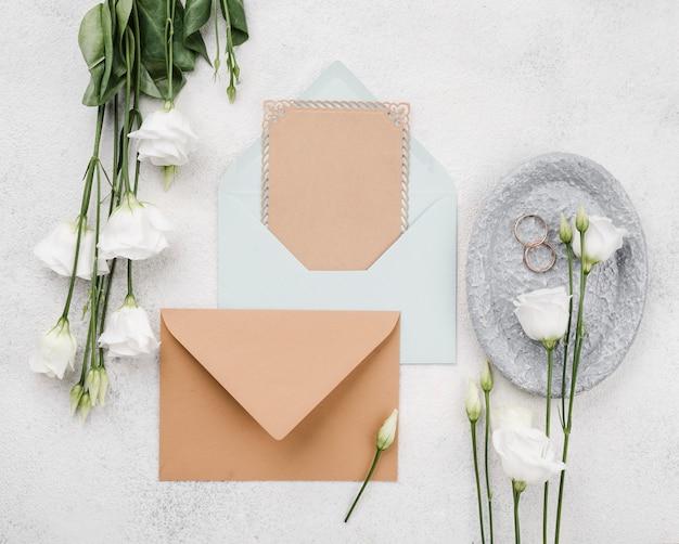 Enveloppes et fleurs de mariage vue de dessus