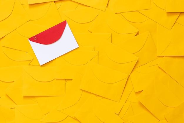 Enveloppes jaunes dispersées sur une table, avec un espace pour le texte sur un papier blanc et une enveloppe rouge en surbrillance. vue de dessus.