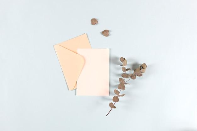 Enveloppes en papier blanc, lettres pour le courrier avec des feuilles d'eucalyptus sur un mur clair