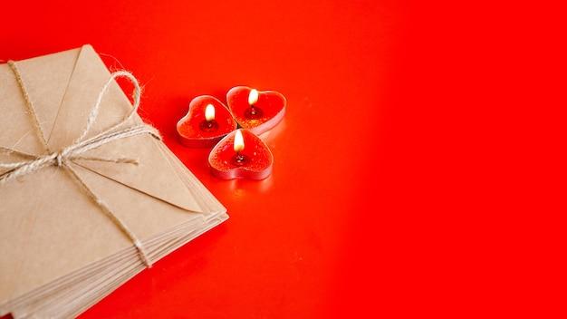 Enveloppes en papier kraft avec des bougies rouges sur fond rouge. concept de la saint-valentin