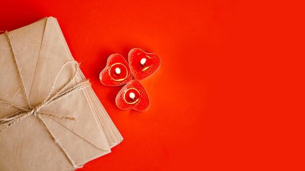Enveloppes en papier kraft avec des bougies rouges sur fond rouge