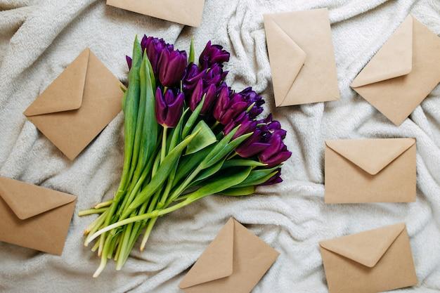 Enveloppes en papier kraft sur plaid beige, fleurs printanières, bouquet de tulipes violettes avec enveloppes.