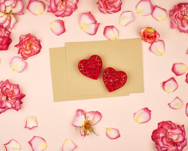 Enveloppes en papier marron et deux coeurs sculptés en rouge au milieu de boutons de rose