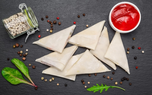 Enveloppes de pâte avec garnitures et sauce épicée.