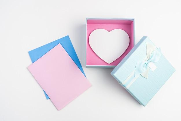 Enveloppes roses et bleues et coffret cadeau avec coeur blanc sur fond clair.