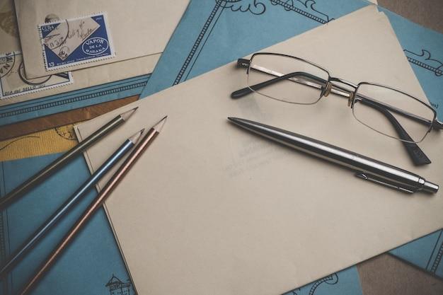 Des enveloppes avec des timbres, un stylo, des crayons, des lunettes sont à la surface. papier à lettres jaune et bleu. vue de dessus. vignette