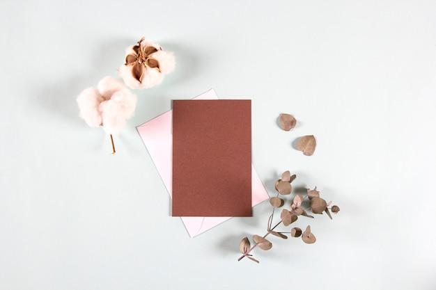 Enveloppes vierges en papier kraft, lettres d'invitation avec des feuilles d'eucalyptus et des fleurs de coton