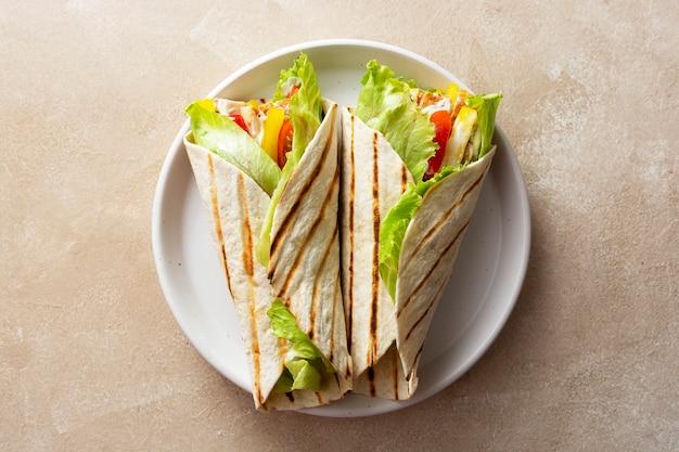 Enveloppez le sandwich burrito ou le kebab avec du pain plat avec des légumes et de la viande blanche. délicieuse nourriture saine, collations à emporter