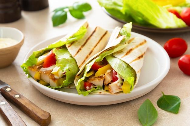 Enveloppez le sandwich burrito ou le kebab avec du pain plat avec des légumes et de la viande blanche. délicieuse nourriture saine