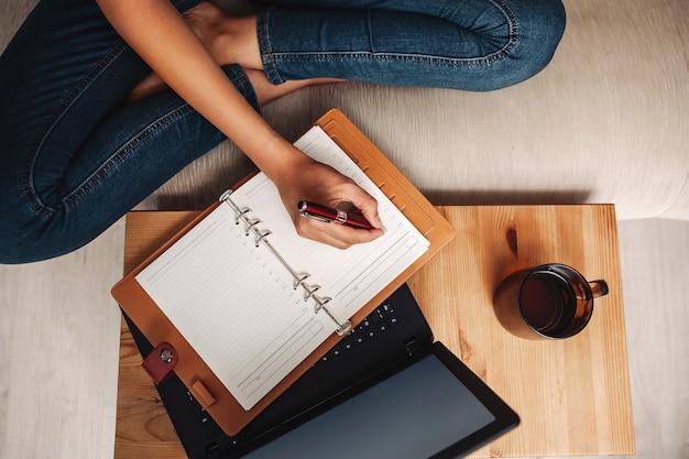 Environnement de travail à domicile, la femme prend des notes dans un cahier qui se trouve sur un ordinateur portable, vue de dessus