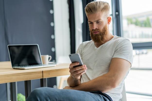 Envoi de sms à un collègue. confiant jeune homme en tenue décontractée intelligente tenant un téléphone intelligent et en le regardant alors qu'il était assis sur son lieu de travail au bureau