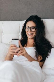 Envoyer un sms à un ami. belle jeune femme souriante et tenant un téléphone intelligent