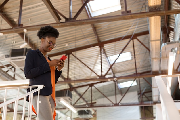 Envoyer un texto à son client. une créatrice à la peau foncée portant un chemisier orange envoie des sms à son client tout en ayant des questions