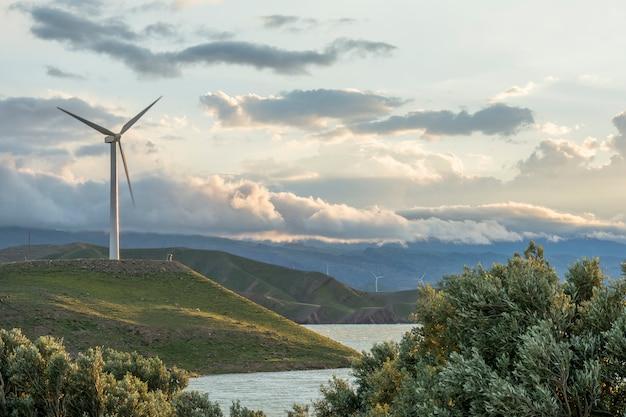 Éolienne sur la colline en face de ciel nuageux