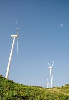 Éoliennes sur les collines produisant de l'électricité sur un ciel bleu avec le fond de la lune. concept de production d'énergie propre et écologique.