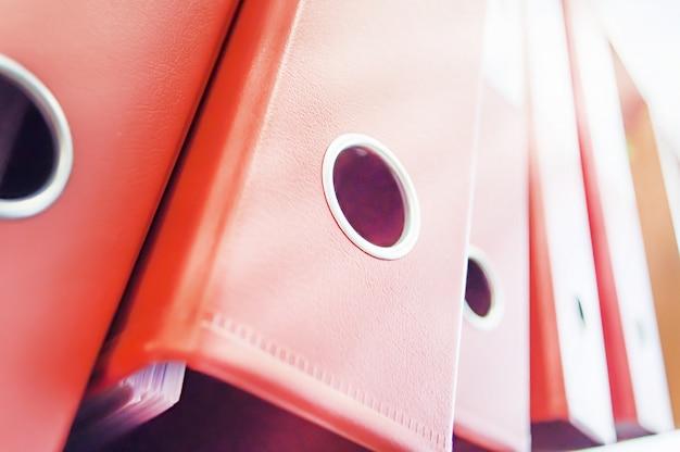 Épais dossiers rouges avec des documents sur une étagère dans le bureau