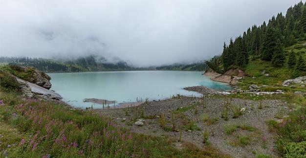 Une épaisse brume blanche sur le lac big almaty, grand réservoir naturel d'eau douce