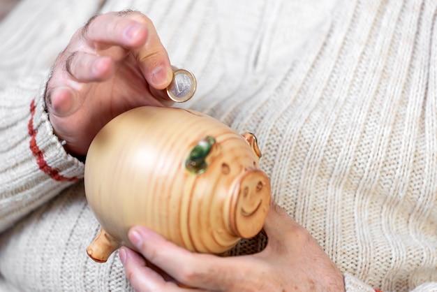 Épargne, argent, assurance annuité, retraite et concept de personnes - gros plan de la main de l'homme senior mettant la pièce dans la tirelire.