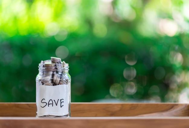 Épargne déposer des pièces dans une bouteille en verre clair