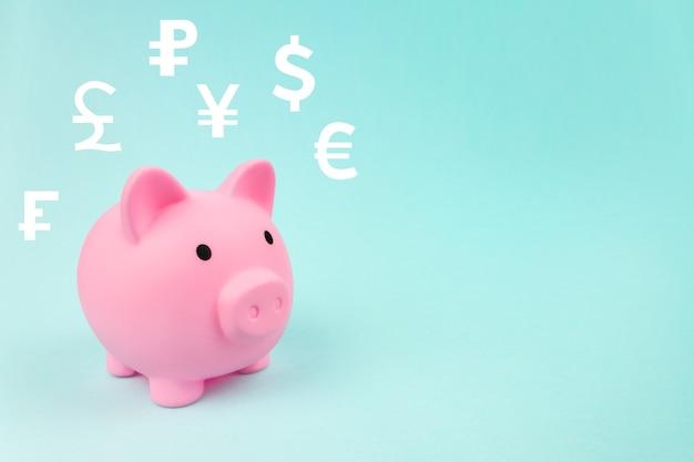 Épargne financière et économie bancaire. tirelire rose avec des devises mondiales d'hologramme numérique sur fond bleu. concept d'échange de devises mondial.