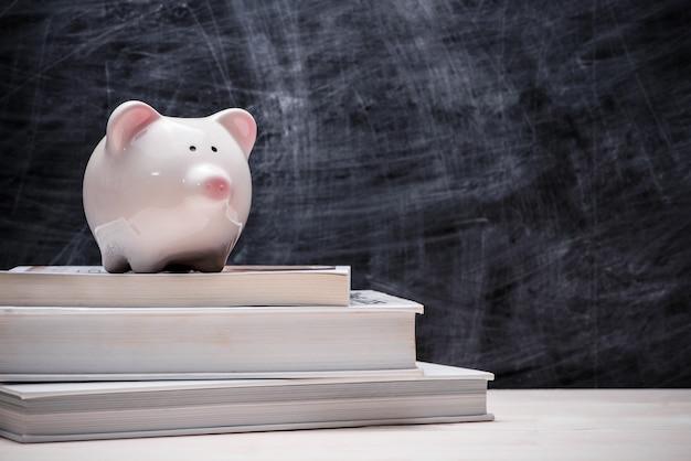 Épargne financière pour l'éducation. tirelire rose sur des livres avec tableau noir.