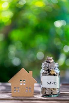 Les épargnes déposent leurs pièces dans une bouteille en verre clair, sur un plancher en bois avec un bokeh en arrière-plan.