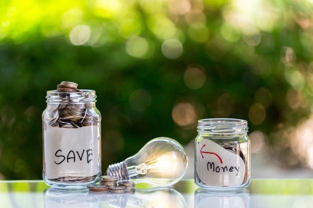Épargnez des pièces dans une bouteille en verre transparent