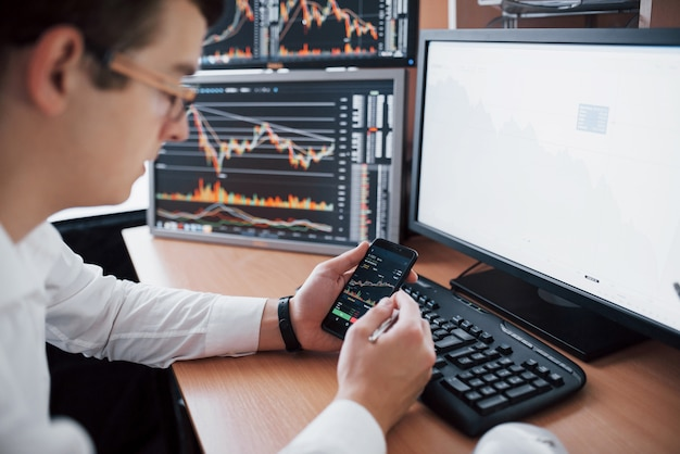 Sur l'épaule et le courtier en bourse négocie en ligne tout en acceptant les commandes par téléphone. plusieurs écrans d'ordinateur remplis de graphiques et d'analyses de données en arrière-plan