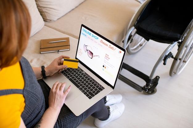 Sur l'épaule de désactive la femme assise sur le canapé et à l'aide d'un ordinateur portable tout en choisissant des lunettes de soleil
