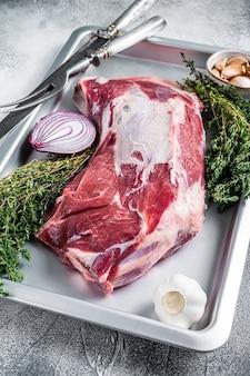 Épaule de mouton d'agneau cru dans un plat allant au four avec du thym et de l'ail