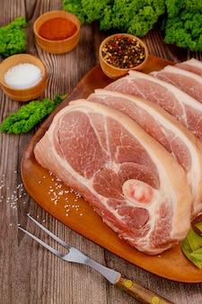 Épaule de porc crue tranchée avec peau sur une surface en bois.