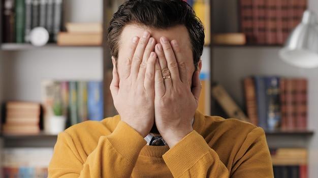 Épaule-visage. un homme barbu étonné dans des lunettes dans un bureau ou un appartement regarde la caméra et se couvre le visage de ses mains pour exprimer sa perplexité. vue rapprochée